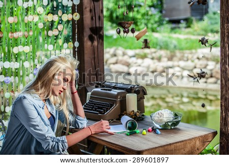 Beautiful young blonde sits in arbor at oak table near vintage typewriter.  - stock photo