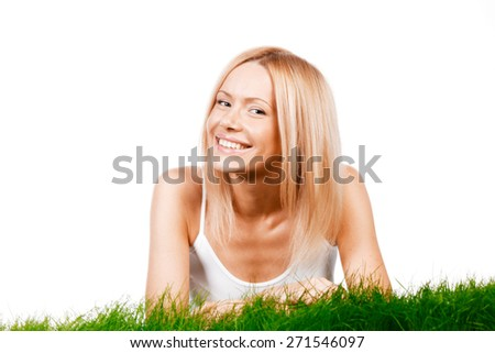 Beautiful young blonde smiling woman lying on grass, isolated on white background - stock photo