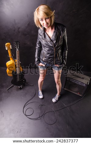 Beautiful young blonde standing in music studio, dressed in black leather jacket with electric guitar on a black background - stock photo