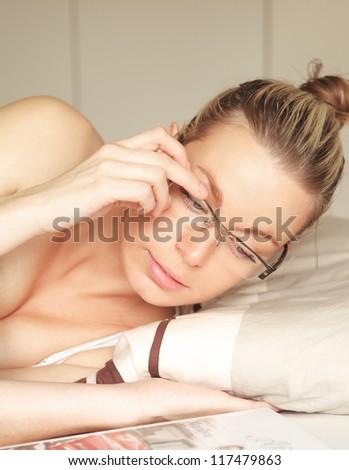 Beautiful young blonde woman confined to bed lying reading with her head raised above the pillow and her hand supporting her glasses - stock photo