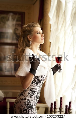 beautiful young blonde woman holding a glass of red wine in restaurant and waiting for her lover. Rich sexy girl in luxury dress black gloves and fur with healthy blond hair. Lady with diamond jewelry - stock photo
