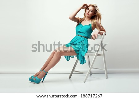 Beautiful young blonde woman in a blue dress and high heels, sitting on a chair  - stock photo