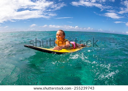 Beautiful young blonde woman in a bright bikini surfing in Mauritius in the Indian Ocean on the background of blue sky, clouds and transparent waves - stock photo