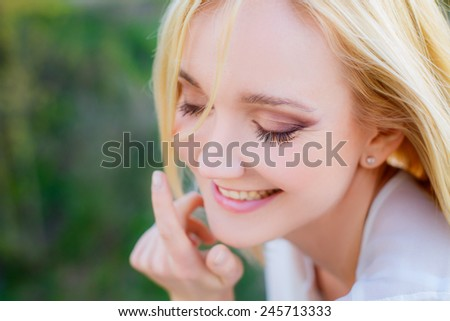 beautiful young blonde woman in a spring park. close-up - stock photo