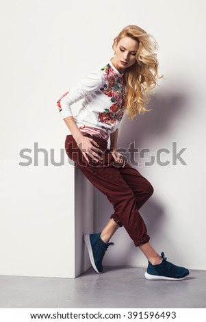 beautiful young blonde woman in a sweatshirt flower with pattern and jeans posing in studio. Fashion photo - stock photo