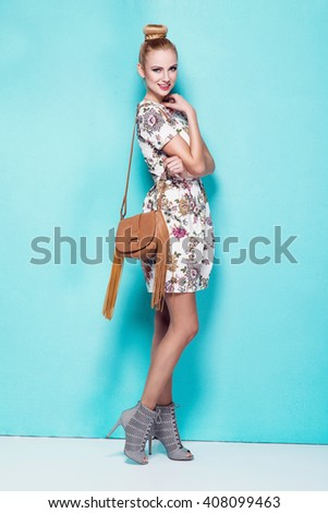 beautiful young blonde woman in nice spring dress, high heels shoe, handbag posing in a studio. Fashion spring summer photo - stock photo