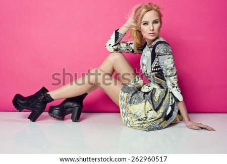 beautiful young blonde woman in nice spring dress, posing in studio. Fashion photo, black boots - stock photo