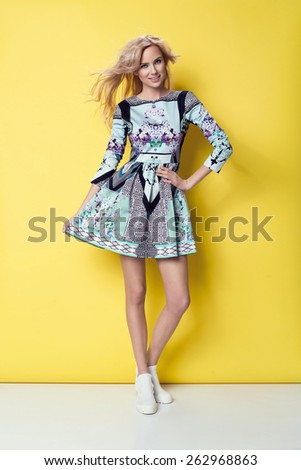 beautiful young blonde woman in nice spring dress, posing in studio. Fashion photo, white boots - stock photo