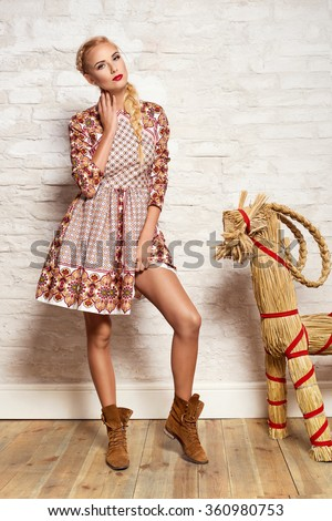 beautiful young blonde woman in nice spring dress, posing on white brick wall. Fashion photo, folklore style. Braid hair style - stock photo