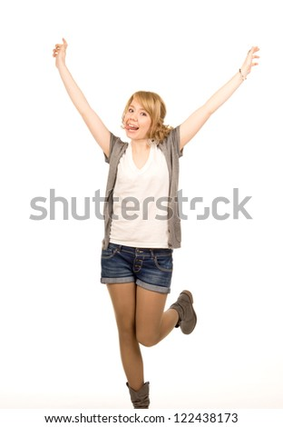 Beautiful young blonde woman in trendy denim shorts jumping for joy with her arms raised in the air isolated on white - stock photo