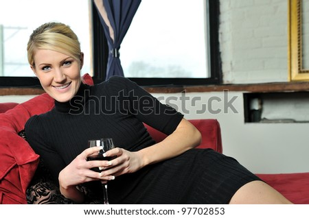 Beautiful young blonde woman lounging on red chaise lounge (chaise longue) in black dress and holding a glass of wine - smiling - stock photo