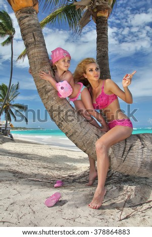 beautiful young blonde woman mon sitting on the trunk of a palm tree with the daughter, little girl princess and background  a beautiful view of the beach, sea at the Dominican Republic, the Caribbean - stock photo
