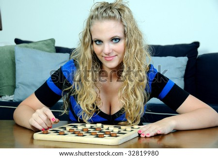 Beautiful young blonde woman playing checkers - stock photo