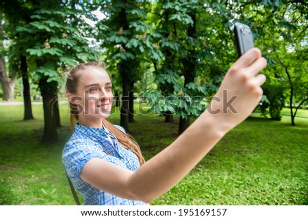 beautiful young blonde woman shooting selfie on mobile phone in the park - stock photo