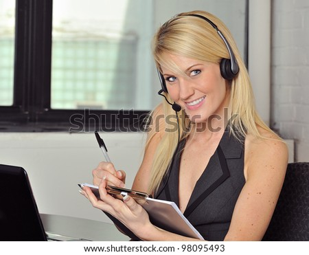 Beautiful young blonde woman sitting in office with headphones - smiling - wearing a vest and taking notes on a clipboard - stock photo