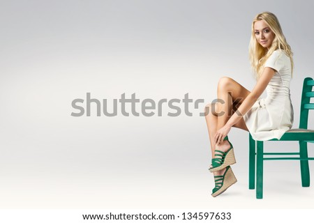 Beautiful young blonde woman sitting on a chair in a trendy wedge shoes and white dress - stock photo