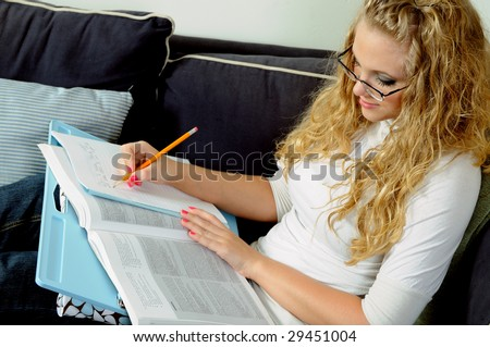 Beautiful young blonde woman studying at home with lap desk - stock photo