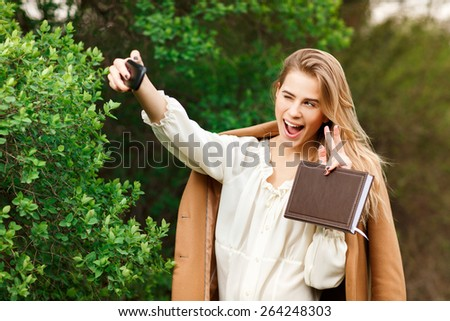 Beautiful young blonde  woman  taking a selfie with smartphone outdoors in park  - stock photo
