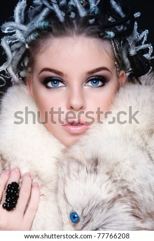 Beautiful young blue-eyed woman with fancy hairstyle of dreads and stylish make-up - stock photo