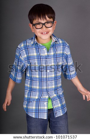 Beautiful young boy making a goofy face with silly glasses looking like a nerd on a grey background - stock photo