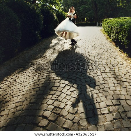 Beautiful young bride and handsome groom holding in the air outdoors near old mansion at sunset shadow silhouette - stock photo