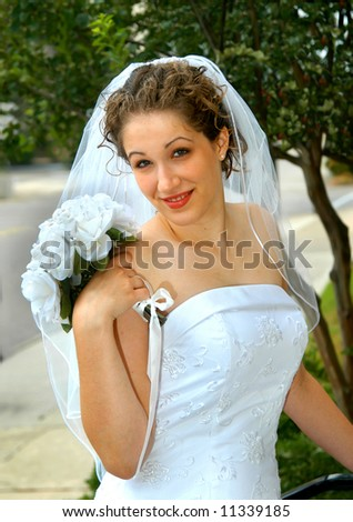 Beautiful young bride holds her bouquet across her shoulder.  She is standing on the steps of church. - stock photo