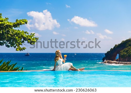 Beautiful young bride in a wedding dress sitting on the edge of the infinity-edge pool and enjoying  cocktail . Tropical sea in the background. - stock photo