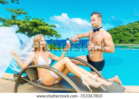 Beautiful young bride in a white bikini, veil and garter on her leg sitting with groom enjoying glass of champagne on the edge of the infinity-edge pool. Tropical sea in the background. - stock photo