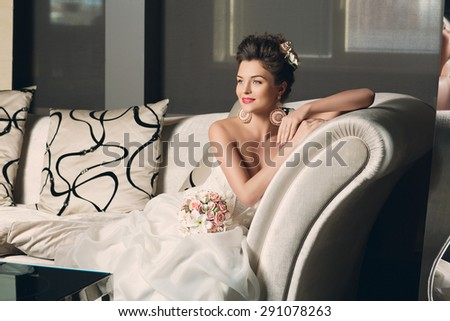 Beautiful young bride in fashionable gown with sitting on sofa. Interior photo. - stock photo