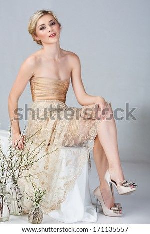 Beautiful young bride in tight gold minidress sitting on studio background  - stock photo