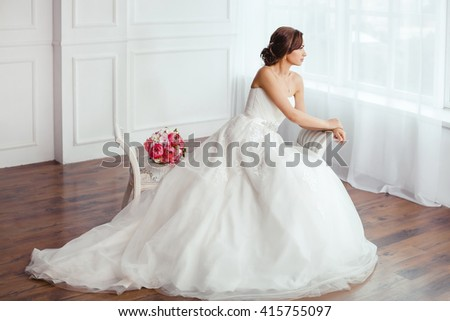 Beautiful young bride in white wedding dress indoors.  Luxuty model sitting on bench with brides bouquet in studio. Girl shows wedding fashion in decorated bright chic interior, high key. - stock photo