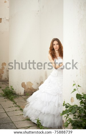 Beautiful young bride looks out for the old column - stock photo