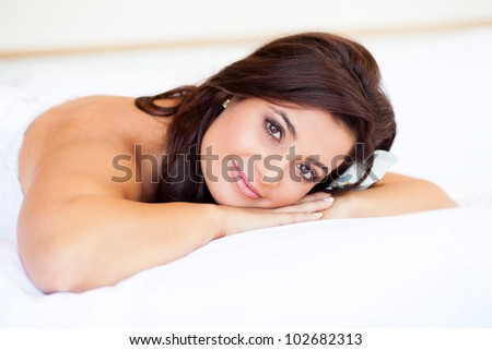beautiful young bride lying on bed - stock photo