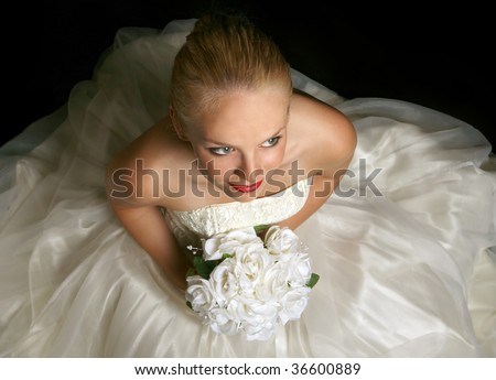 Beautiful Young Bride Sitting Holding Flowers - stock photo