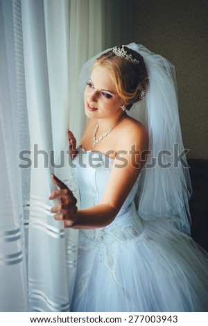 beautiful young bride standing beside a large window waiting. Beautiful caucasian bride getting ready for the wedding ceremony - stock photo