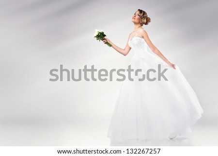 beautiful young bride wearing wedding dress holding white flowers - stock photo