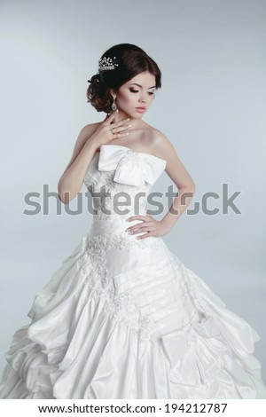 Beautiful young bride woman posing in wedding dress isolated on gray background. - stock photo