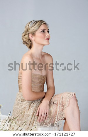 Beautiful young bright in tight golden minidress and embroidred lace sitting on studio background  - stock photo