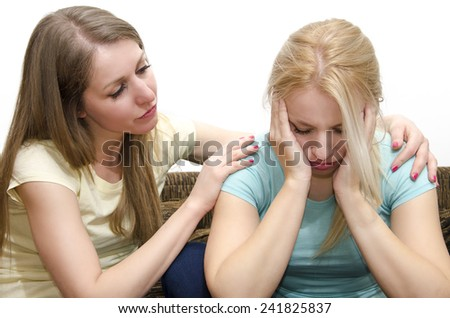Beautiful young brunette comforting sad friend - stock photo