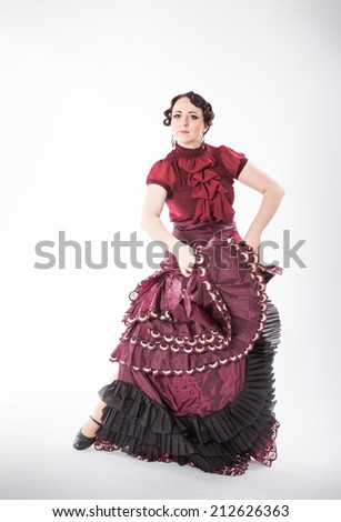 beautiful young brunette female spanish flamenco dancer in red blouse and vinous flamenco skirt dancing with her arms and flying skirt in studio on gray background - stock photo
