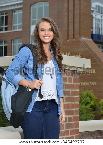 Beautiful young brunette female student carrying backpack on campus - stock photo