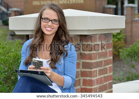 Beautiful young brunette female student sitting and looking at her tablet computer and smartphone - stock photo