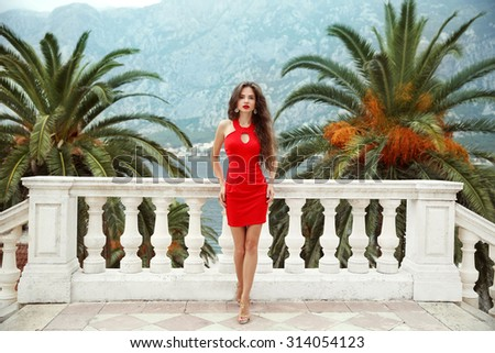 Beautiful young brunette girl model in red dress standing on Balcony view on palms and sea shore Kotor, Montenegro. - stock photo