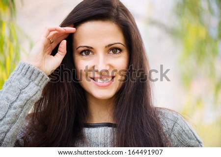 Beautiful young brunette girl portrait at park - stock photo