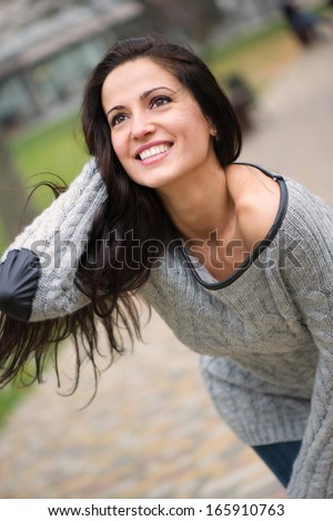 Beautiful young brunette girl smiling at park - stock photo