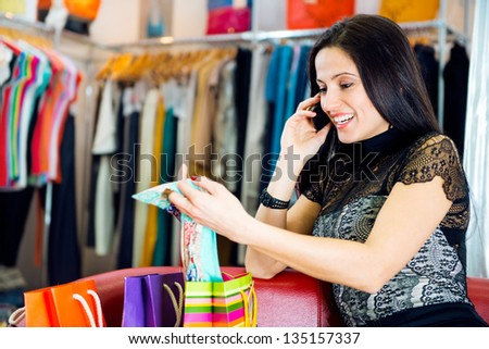 Beautiful young brunette girl talking via phone in clothes boutique - stock photo