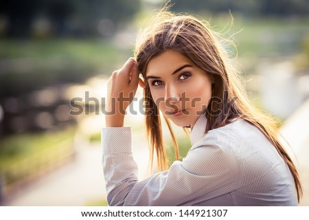 Beautiful young brunette girl with long hair. - stock photo