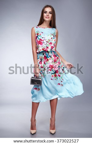 Beautiful young brunette girl woman lady dressed in a pale blue silk handbag and belt Accesories long dark hair, make-up and cosmetics, catalog of everyday and festive dress, sexy style and fashion - stock photo
