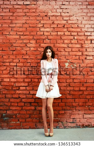 Beautiful young brunette in pink dress posing outdoor near red brick wall - stock photo
