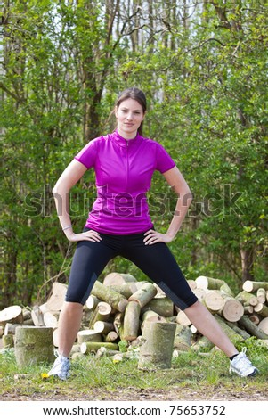 Beautiful young brunette in sportswear outdoors doing stretch exercises - stock photo